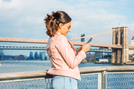 Young American Woman traveling in New York, wearing pink leather jacket, sunglasses, standing by East River, looking down, texting on cell phone, smiling. Brooklyn, Manhattan bridges on background.