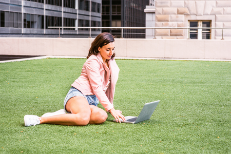 Young American College Student Studying n New York, wearing light pink leather jacket, ripped Denim shorts, white sneakers, bending legs, sitting on green lawn on campus, working on laptop computer. Banco de Imagens