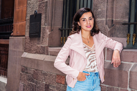 Woman Street Casual Fashion in New York. Young Happy American Lady wearing light pink leather jacket, v neck patterned undershirt, blue Denim jeans, standing by old style wall with windows, smiling. Banco de Imagens