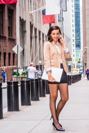Young American Woman traveling, working in New York, wearing beige blazer, black short skirt, tights, leather shoes, holding laptop computer, standing on street, looking down, talking on cell phone.