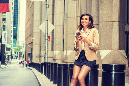 Young American Business Woman traveling, working in New York City, wearing beige blazer, black short skirt, tights, sitting on pillar on old narrow street in Manhattan, texting on cell phone, smiling. Banco de Imagens