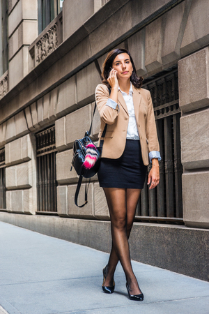 Young American Woman traveling, working in New York, wearing beige blazer, white shirt, black short skirt, tights, leather shoes, carrying shoulder bag, walking on old street, talking on cell phone.