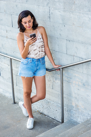 Modern Reading. Young American Woman wearing summer spaghetti strap v neck leisure tank top, blue ripped Denim shorts, white sneakers, standing by railing by wall in New York City, reading cell phone.