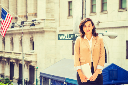 Young American Woman traveling, working in New York City, wearing beige color jacket, black skirt, holding tablet computer, standing on Wall Street outside vintage office building, looking forward. Banco de Imagens
