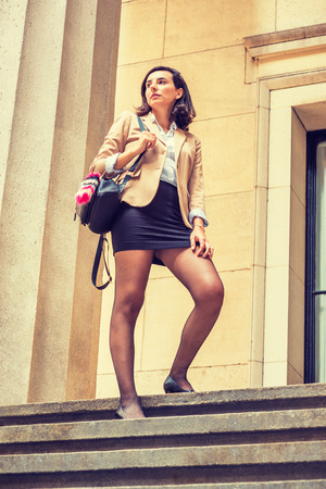 Young Businesswoman Fashion in New York, wearing beige blazer, white shirt, black short skirt, tights, leather shoes, carrying shoulder bag, standing on stairs outside office building, looking up.