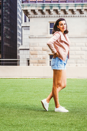 Portrait of Young American Female College Student in New York City, wearing light pink leather jacket, blue ripped Denim shorts, white sneakers, hands on hips, standing on green lawn on campus.
