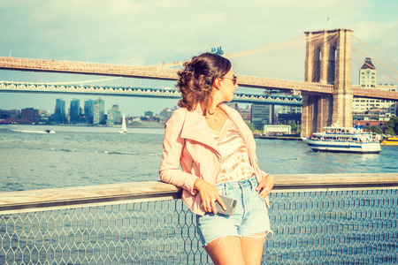 Young American Woman traveling in New York, wearing pink leather jacket, blue ripped Denim shorts, sunglasses, standing by river, looking back. Brooklyn, Manhattan bridges, boats on background. Banco de Imagens