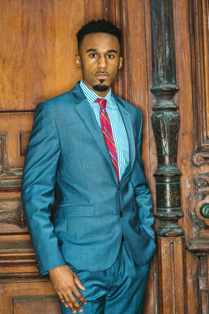 Portrait of Young African American Businessman with beard in New York, wearing gray blue suit, white patterned shirt, purple patterned tie, standing by brown vintage office door, looking forward.