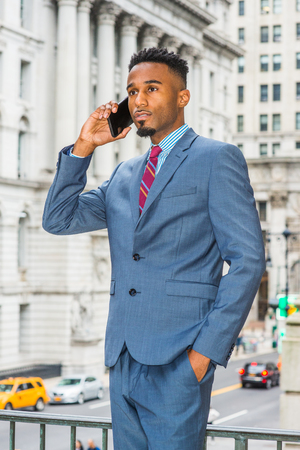 Young African American Businessman with beard working in New York, wearing dark sky blue suit, violet red patterned tie, standing on street outside vintage office building, talking on cell phone.