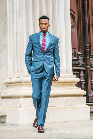 Young African American Businessman with beard working in New York, wearing sky blue suit, violet red patterned tie, dark purple leather shoes, holding laptop computer, walking out from office door way. 写真素材