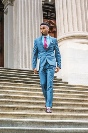 Young African American Businessman with beard working in New York, wearing sky blue suit, violet red patterned tie, dark purple leather shoes, holding laptop computer, walking down stairs from office.  Banco de Imagens