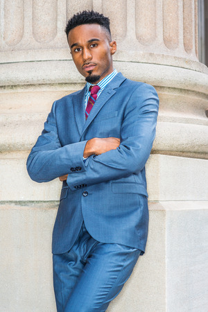 Portrait of Young African American Businessman with beard in New York, wearing dark sky blue suit, white patterned shirt, violet red patterned tie, crossing arms, standing outside office building.  Banco de Imagens