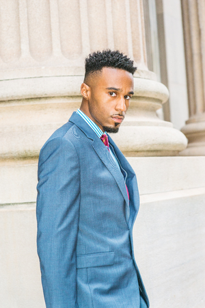 After work. Young African American Businessman with beard, short afro hair, working in New York, wearing dark sky blue suit, violet red patterned tie, walking out from office building, looking away.  Banco de Imagens