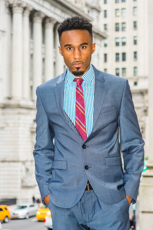 Portrait of Young African American Businessman with beard in New York, wearing dark sky blue suit, white patterned shirt, violet red patterned tie, standing on street by old office building, looking.