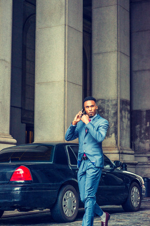 Young African American Businessman with beard traveling, working in New York, wearing blue suit, walking on vintage street with high columns in Manhattan, passing parked car, talking on cell phone.