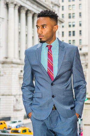 Portrait of Young African American Businessman with beard in New York, wearing dark sky blue suit, white patterned shirt, violet red patterned tie, standing on street by office building, looking away.