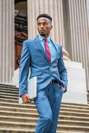 Young African American Businessman with beard working in New York, wearing dark sky blue suit, white striped shirt, violet red patterned tie, walking down stairs from old style office building.