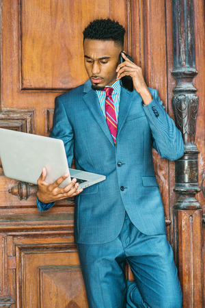 Young African American Businessman with beard working in New York, wearing sky blue suit, violet red patterned tie, standing by brown office door, working on laptop computer, talking on cell phone.