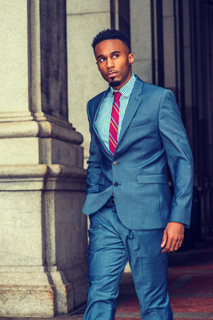 Young African American Businessman with beard traveling, working in New York, wearing dark sky blue suit, white striped shirt, violet red patterned tie, walking by columns on vintage street, looking.