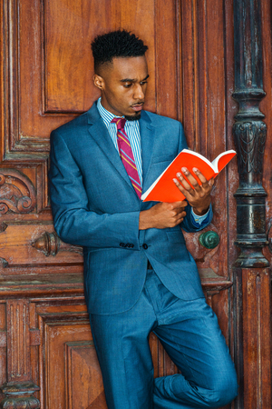 Power of Reading. Way to Success. Young African American Man with beard working, studying in New York, wearing gray blue suit, patterned tie, standing by brown vintage office door, reading red book.