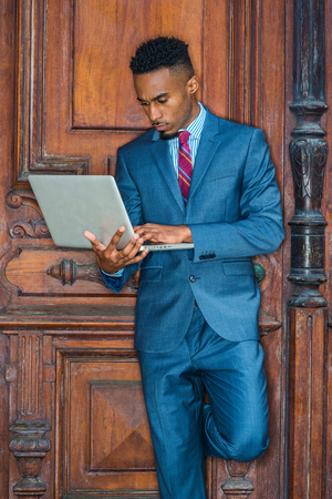 Way to Success. Young African American Businessman with beard working in New York, wearing sky blue suit, violet red patterned tie, standing by brown vintage office door, working on laptop computer.