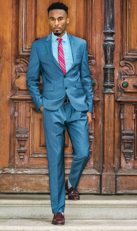 53798643fe Stock Photo - Young African American Businessman with beard in New York,  wearing gray blue suit, white patterned shirt, purple patterned tie, ...
