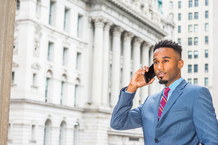 Young African American Businessman with beard working in New York, wearing dark sky blue suit, violet red patterned tie, standing on street outside vintage office building, talking on cell phone. Banco de Imagens