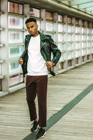 Young Man Casual Fashion in New York. Young African American Guy with beard, wearing black leather jacket, white shirt, black pants, sneakers, standing on walk way with glass wall and wooden floor.