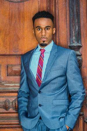 Portrait of Young African American Businessman with beard in New York, wearing gray blue suit, white patterned shirt, purple patterned tie, standing by brown vintage office door, looking forward. Banco de Imagens