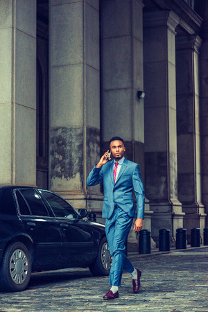 Young African American Businessman traveling, working in New York, wearing blue suit, violet red patterned tie, purple leather shoes, walking on vintage street with high columns, talking on cell phone