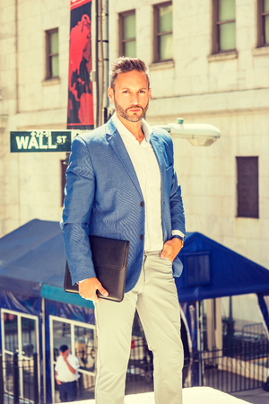 Young European Businessman with beard traveling, working in New York City, wearing blue blazer, white shirt, holding briefcase, standing on street outside office by Wall Street sign, looking forward.