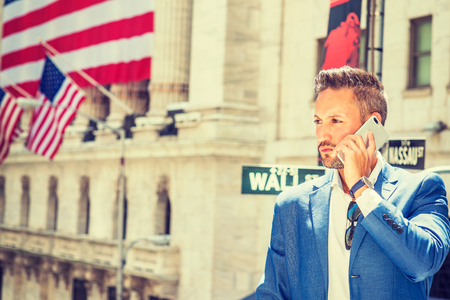 Young European Businessman with beard traveling, working in New York, wearing blue blazer, sunglasses hanging on white shirt, standing outside office building on Wall Street, talking on cell phone.