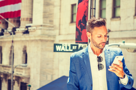 Young European Businessman with beard traveling, working in New York City, wearing blue blazer, sunglasses hanging on white shirt, standing on Wall Street, looking at cell phone, reading, texting. Banco de Imagens