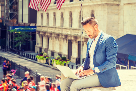 Young European Businessman with beard traveling, working in New York City, wearing blue blazer, gray pants, sitting on street outside office building, looking down, typing, working on laptop computer. Banco de Imagens