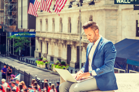 Young European Businessman with beard traveling, working in New York City, wearing blue blazer, sitting on street outside office building by Wall Street sign, typing, working on laptop computer.