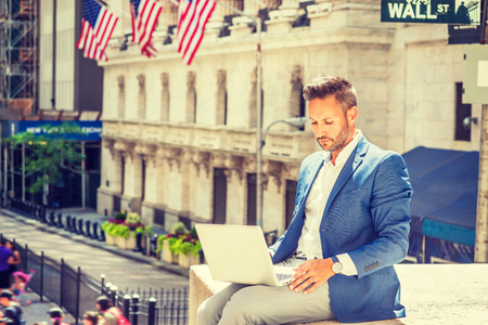 Young European Businessman with beard traveling, working in New York City, wearing blue blazer, sitting on street outside office building by Wall Street sign, reading, working on laptop computer.