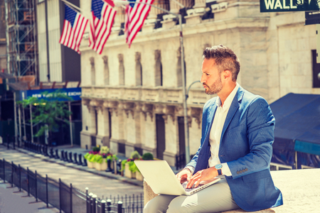 Young European Businessman with beard traveling, working in New York City, wearing blue blazer, sitting on street outside office building by Wall Street sign, working on laptop computer, thinking.