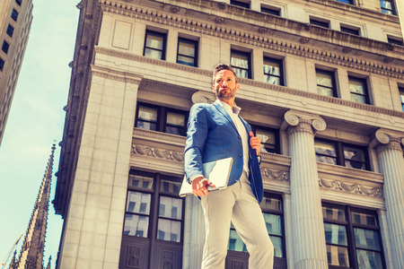 Young European Businessman with beard traveling, working in New York City, wearing blue blazer, gray pants, holding laptop computer, standing on street outside old office building, looking forward.