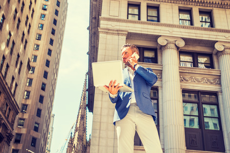 Young European Businessman with beard traveling, working in New York City, wearing blue blazer, gray pants, standing outside old office building, working on laptop computer, talking on cell phone. Banco de Imagens
