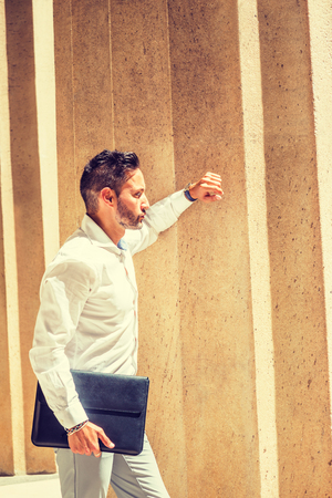 Thinking outside. Young European Businessman with beard, wearing white shirt, holding briefcase, standing outside office in New York City, under sunshine, arm resting on column, thinking. Side View.