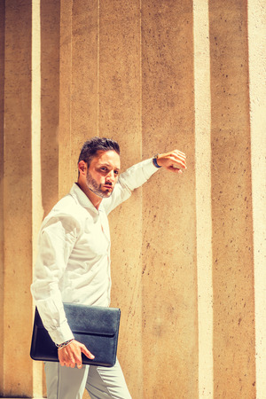 Thinking outside. Young European Businessman with beard, wearing white shirt, holding briefcase, standing outside office in New York City, under sunshine, arm resting on column, looking away, thinking. Banco de Imagens