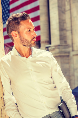 Thinking outside. Young European Businessman with beard, wearing white shirt, holding briefcase, standing outside office building on street in New York City, under sunshine, looking, thinking.