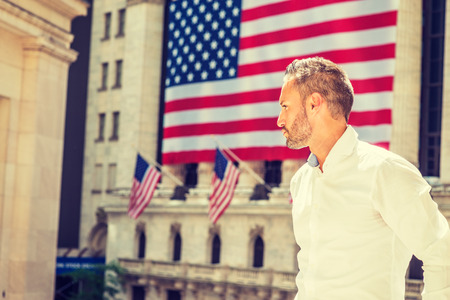 Young Sexy European Man with beard traveling in New York in summer, wearing long sleeve white shirt, standing outside old style office building with American flags under sun, looking forward.