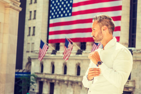 Young European Man with beard traveling in New York in summer, wearing long sleeve white shirt, wristwatch, standing office building with American flags under sun, hand touching cuff, looking forward.