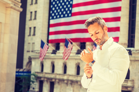 Young European Man with beard traveling in New York in summer, wearing long sleeve white shirt, wristwatch, standing office building with American flags under sun, looking down, hand buttoning cuff. Banco de Imagens
