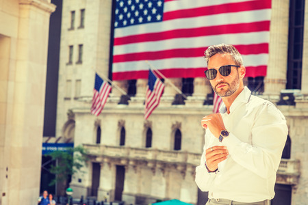 Young European Man with beard traveling in New York in summer, wearing long sleeve white shirt, sunglasses, wristwatch, standing office building with American flags under sun, hand buttoning cuff. Banco de Imagens