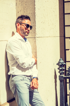 Thinking outside. Young European Businessman with beard, wearing white shirt, sunglasses, standing against wall outside office in New York City, under sun, thinking, lost in thought. Banco de Imagens