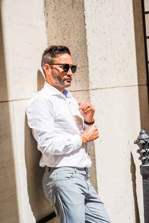 Thinking outside. Young European Businessman with beard, wearing white shirt, sunglasses, standing against wall outside office in New York City, under sun, hand touching cuff,  lost in thought.
