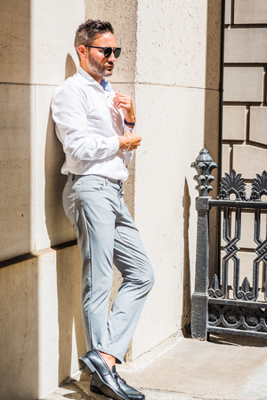 Young European Businessman with beard, wearing white shirt, gray pants, black leather shoes,  sunglasses, standing against wall outside office in New York City, under sun, hand touching cuff.