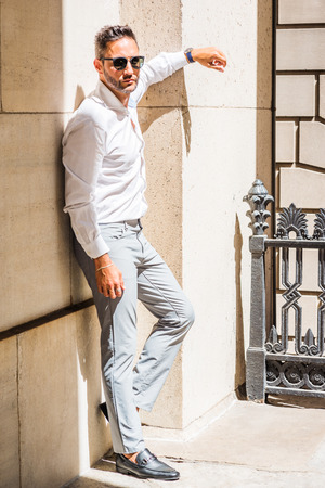 Thinking outside. Young European Businessman with beard, wearing white shirt, gray pants, black leather shoes,  sunglasses, standing against wall outside office in New York City, under sun, thinking.